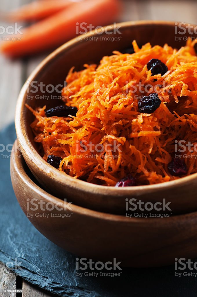 Carrot salad with raisins on the wooden table, stock photo