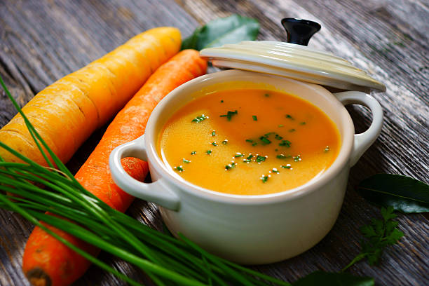 Carrot soup in a white bowl with lid and carrots on the side Carrot soup on wooden background vegetable soup stock pictures, royalty-free photos & images