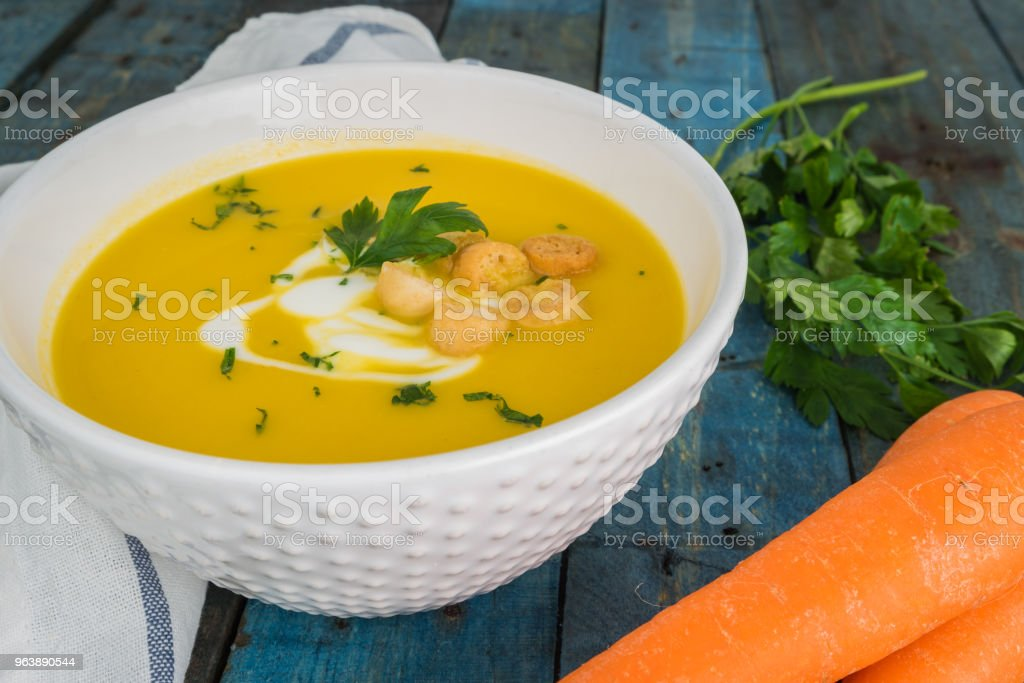Carrot soup with cream and parsley on wooden background - Royalty-free Bowl Stock Photo