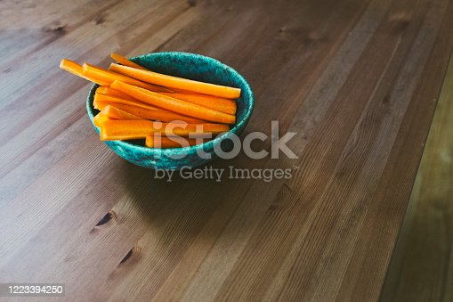 May 6, 2020 - Warsaw, Poland: Bowl Of Chopped Carrots sticks on a wooden brown tabletop