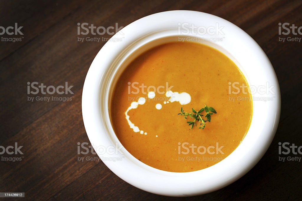 Carrot yam potato creamy soup with cream and thyme royalty-free stock photo
