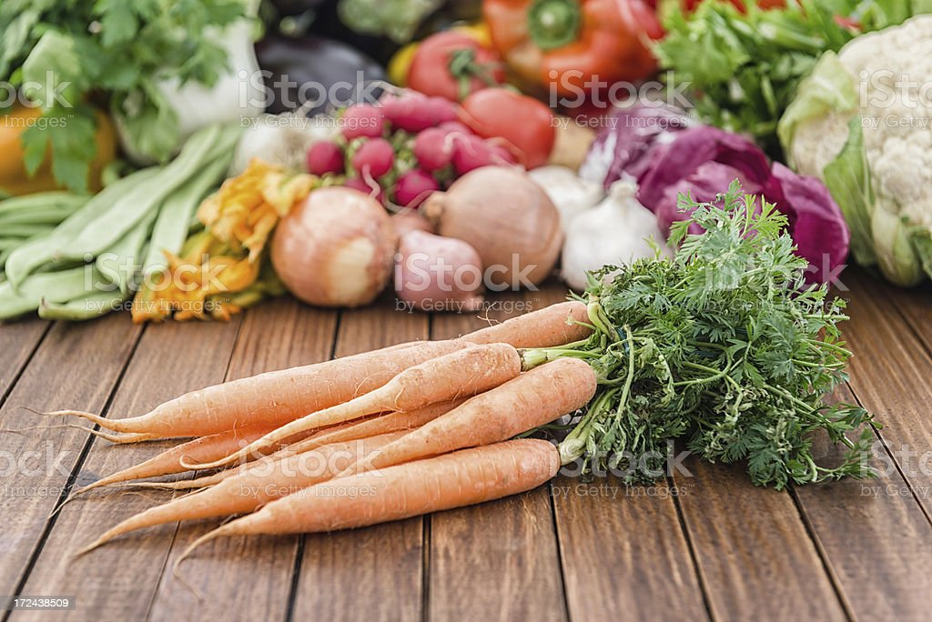 Carrots on wood plank with others vegeables royalty-free stock photo