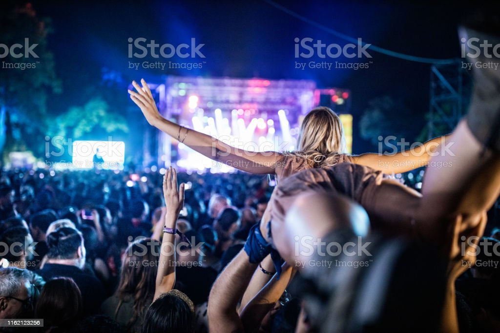 Rear view of carefree woman being held by crowd of people during...