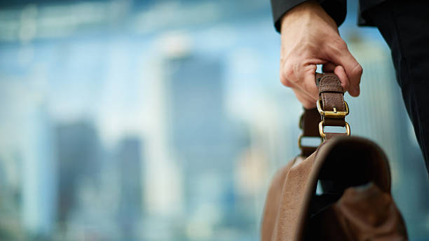 Carrying briefcase Human hand holding a handle of brown leather briefcase briefcase stock pictures, royalty-free photos & images
