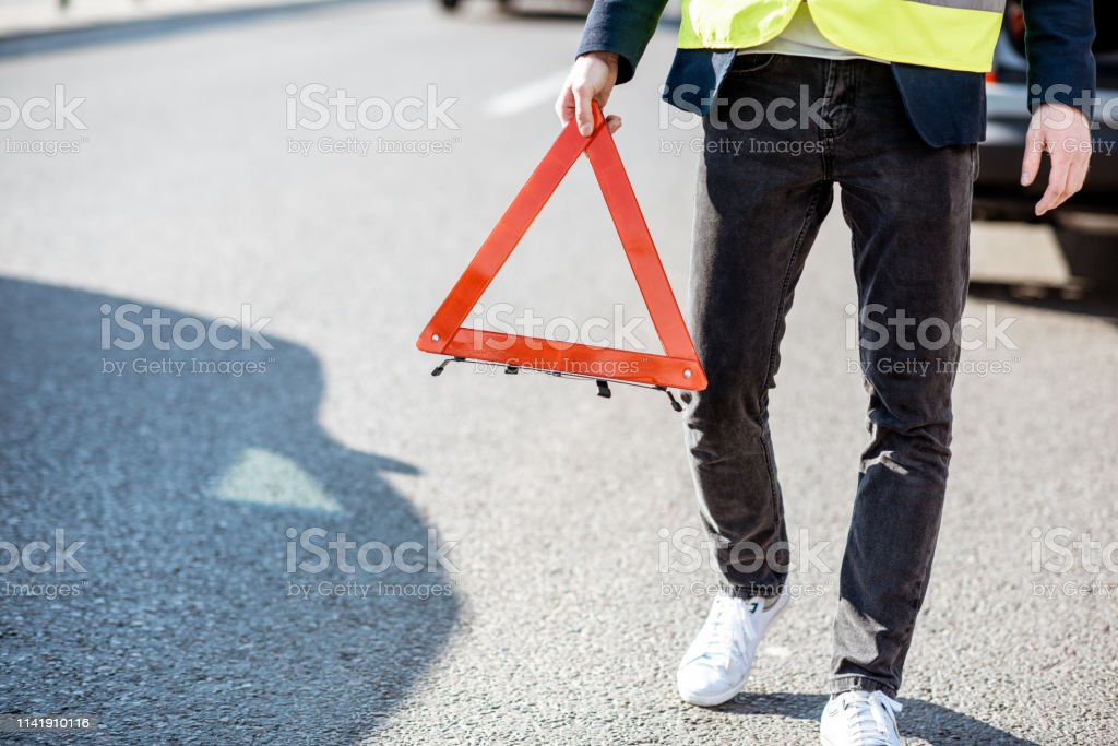 Man carrying emergency triangle sign on the road, having a problem...