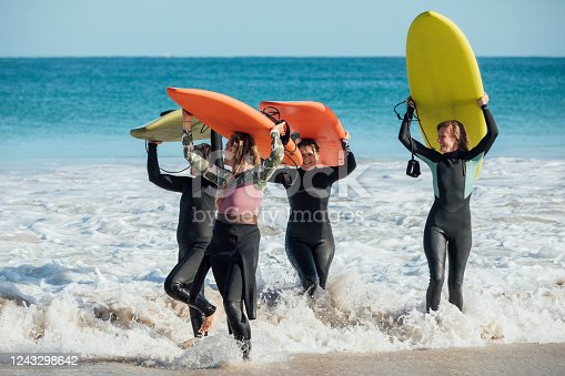 Group of mature women carrying their surfboards out of the sea.