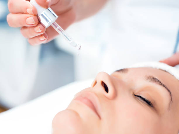 carrying out cosmetological procedure - serum stock photos and pictures