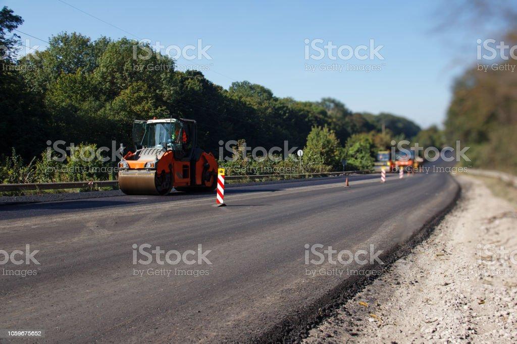 asphalt roller stacking and pressing hot lay of asphalt. Machine...