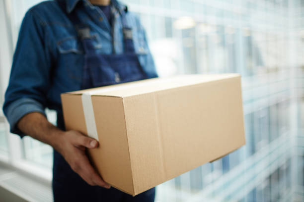 Carrying package Relocation service worker or courier carrying packed carton box while distributing it to receiver carrying stock pictures, royalty-free photos & images