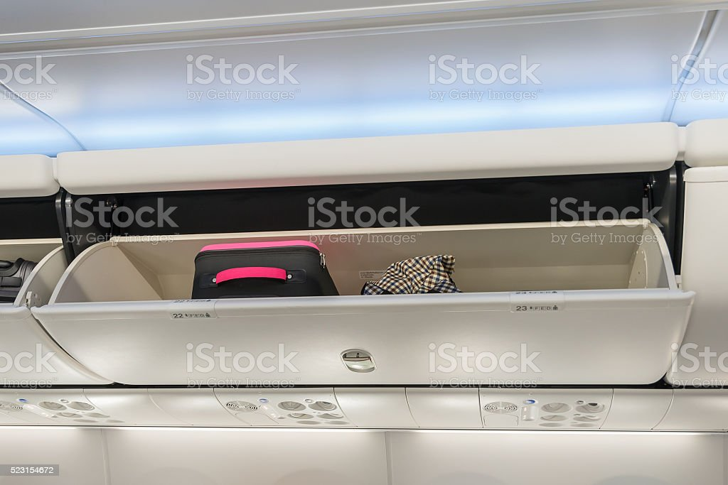 Carry-on luggage in overhead storage compartment on airplane. stock photo