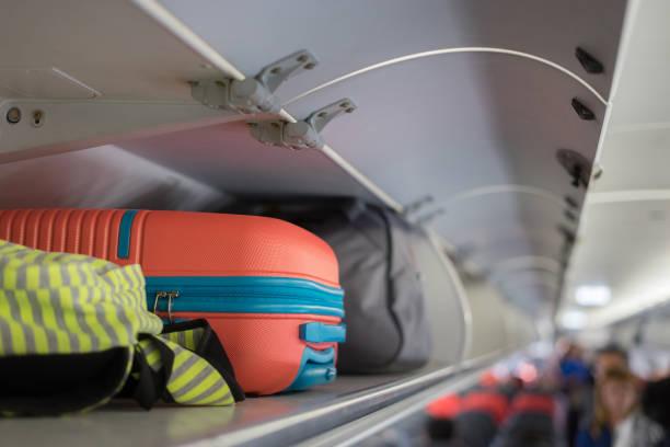 equipaje de mano en el estante superior sobre la cabeza en el avión, pasajero poner bolsa compartimiento de cabina de aire nave clase ejecutiva, color vintage, copiar espacio - suministros escolares fotografías e imágenes de stock