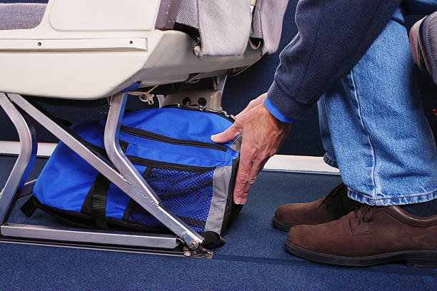 Carry-on Luggage Airplane passenger stowing his carry-on luggage under the seat in front of him. carry on luggage stock pictures, royalty-free photos & images