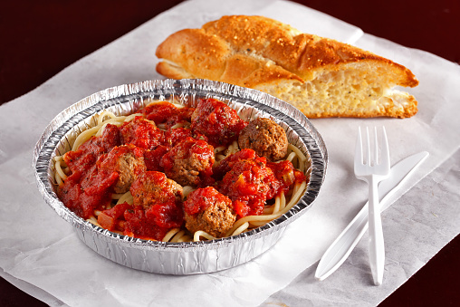Italian spaghetti and meatballs with tomato based sauce and a slice of crusted bread in an aluminum take-out container