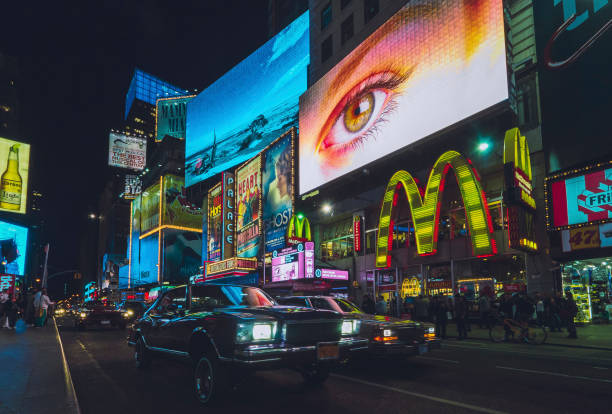 Cars and billboards at night in New York City stock photo