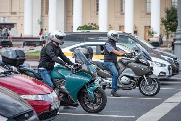 carros e motos na estrada esperar por um semáforo - foto de acervo