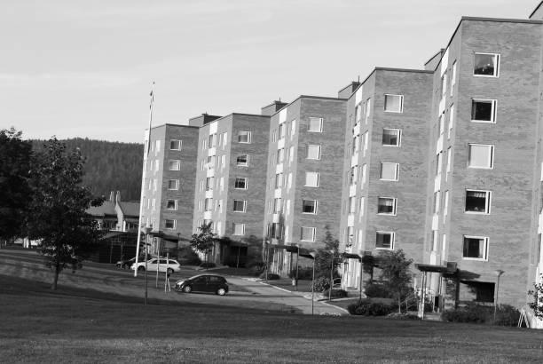Coches y residentes fuera de un bloques de apartamento bonito barrio residencial de Nacksta ciudad de Sundsvall, Suecia. Blanco y negro - foto de stock