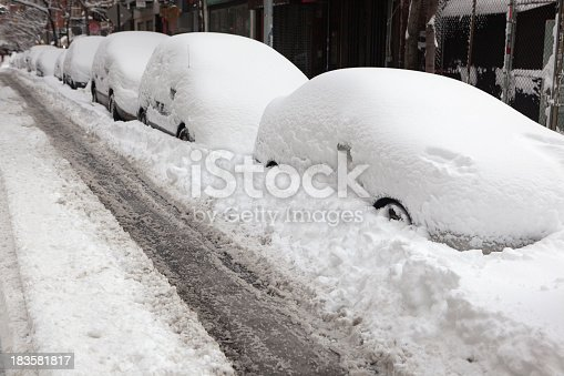 snow covered cars on a street in downtown Manhattan,NYC after a severe winter storm the previous evening.