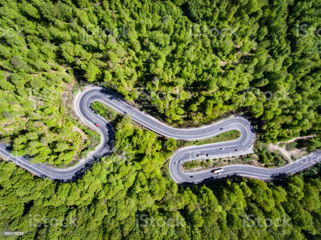 Cars and trucks on winding road trough the forest, Transilvania, Romania stock photo