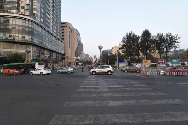중국 도시 쿤밍에서 당나라에서 서쪽과 동쪽 탑을 연결하는 거리에서 자동차가 운전하고 있습니다. - 쿤밍 뉴스 사진 이미지
