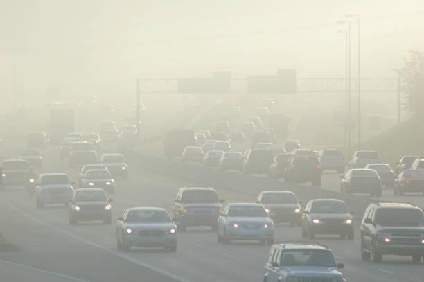 coches en la hora pico en dirección a través de grosor smog - contaminación ambiental fotografías e imágenes de stock