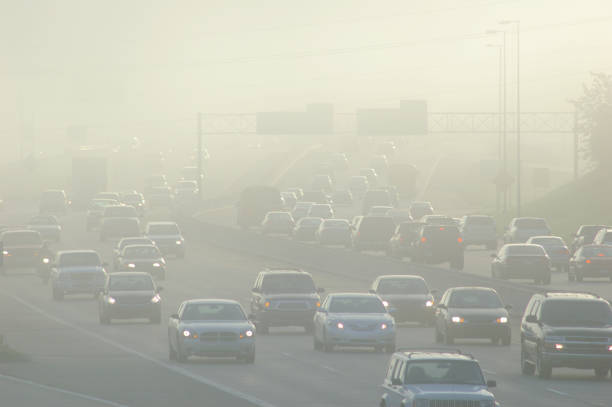 cars at rush hour driving through thick smog - pollution stock pictures, royalty-free photos & images