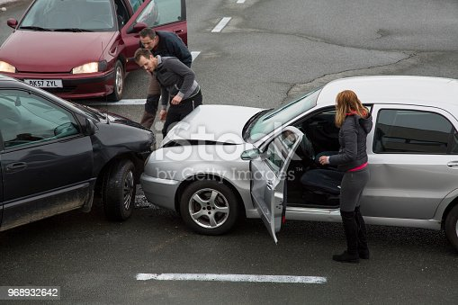 Two men looking at cars collision on road, woman standing near car.
