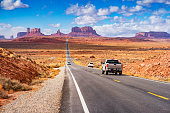 Cars drive at Forrest Gump Point in Monument Valley, Utah, USA on a sunny day