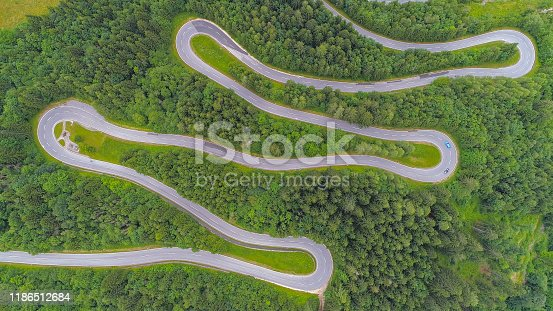 AERIAL, TOP DOWN: Motorcycles and cars driving on zig zag undulating road through lush dense spruce forest on mountain slope. Curvy switchback highway with hairpin turns snaking through the woods