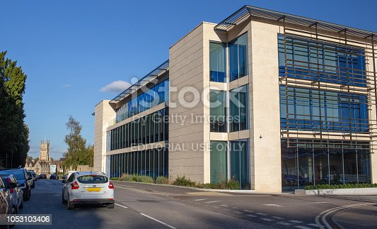 4th October, 2018 - Cars driving by the new modern headquarters of St. James's Place in Cirencester Gloucestershire, with the Parish Church of St John Baptist in the distance. St. James's Place is a UK-based wealth management business