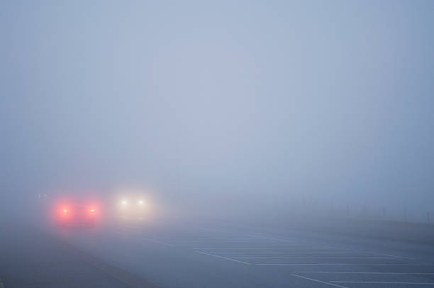 Cars driving in thick fog stock photo