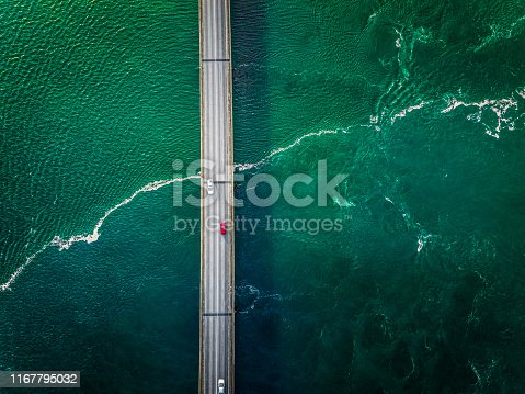 Cars driving over a bridge. Colourful sea passing under a big bridge. Red car is popping out.