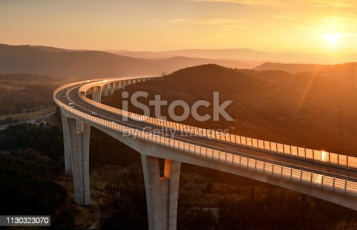 Cars driving on a highway viaduct at beautiful sunset