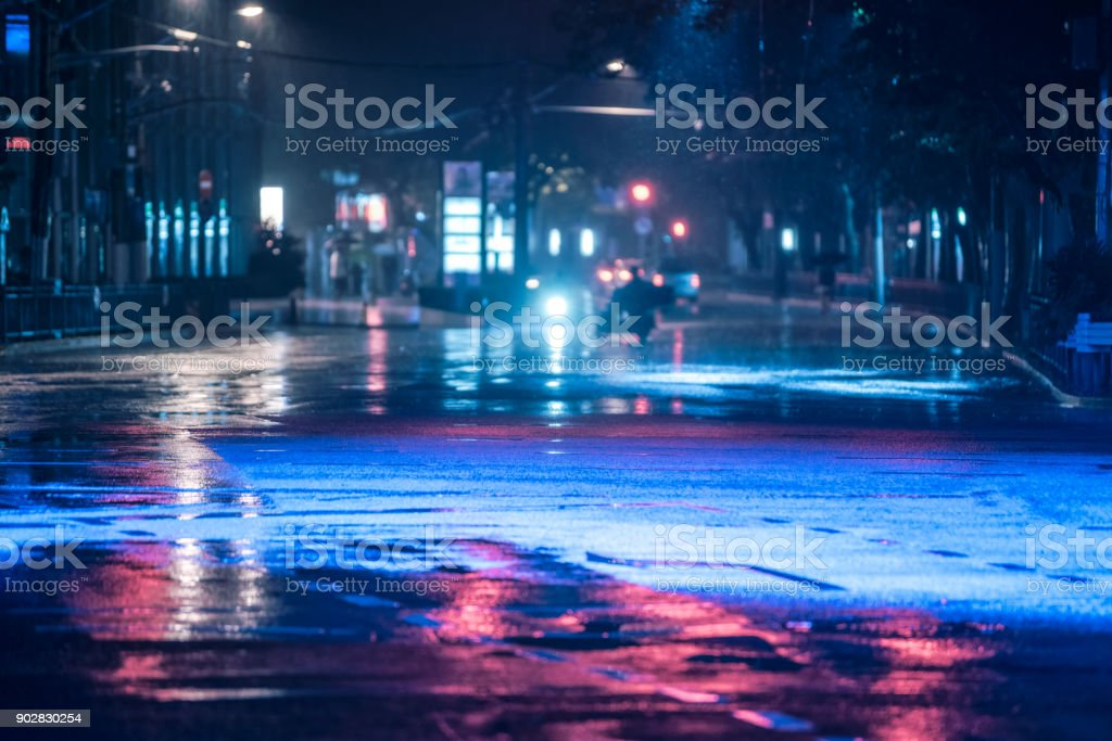 Cars driving on wet road in the rain and colored lights reflected on the wet asphalt road foto stock royalty-free
