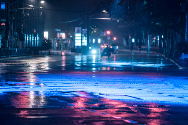 yağmur ve renkli ışıklar ıslak yolda sürüş araba ıslak asfalt yolda yansıyan - islak stok fotoğraflar ve resimler