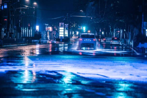 Autos fahren auf nasser Fahrbahn bei Regen und bunten Lichtern reflektiert auf dem nassen Asphaltweg – Foto