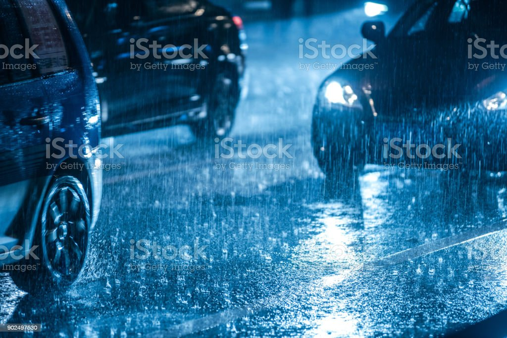Cars driving on wet road in the rain with headlights stock photo