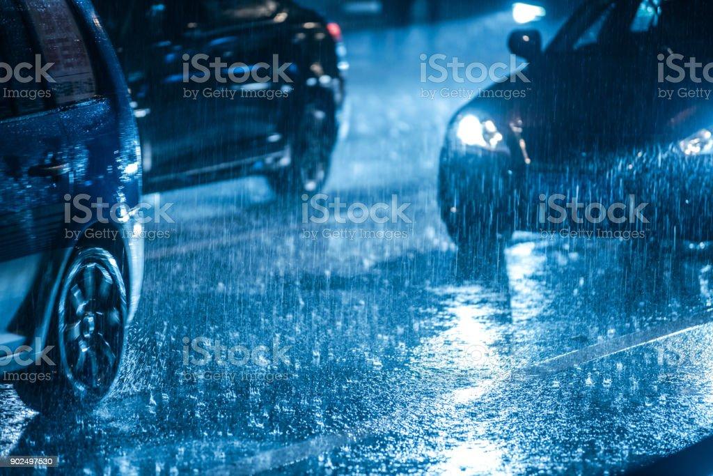 Conducir en el camino mojado en la lluvia con faros de coches - foto de stock