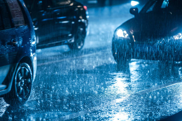 cars driving on wet road in the rain with headlights - deszcz zdjęcia i obrazy z banku zdjęć