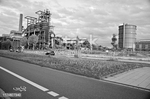 Black and white image of cars driving past Hochofenplatz - a decommissioned steel factory in Phoenix West, Dortmund - Germany