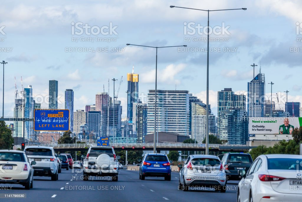 Cars Driving Towards The City Cbd With Road Signage To