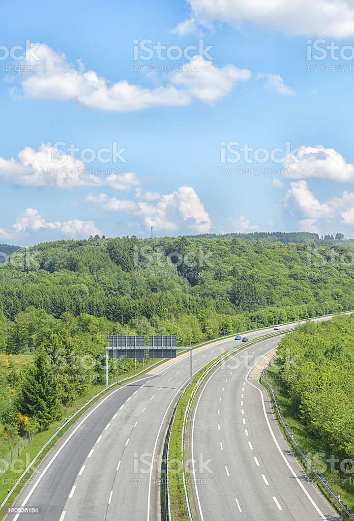 Cars in distance on empty highway royalty-free stock photo