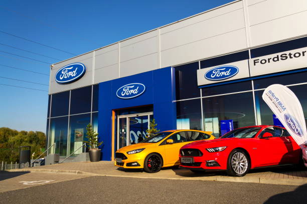 cars in front of ford motor company dealership building - ford focus stock photos and pictures