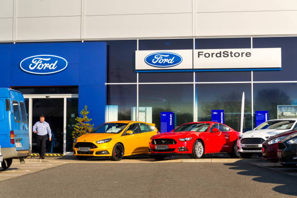 Cars in front of Ford motor company dealership building stock photo