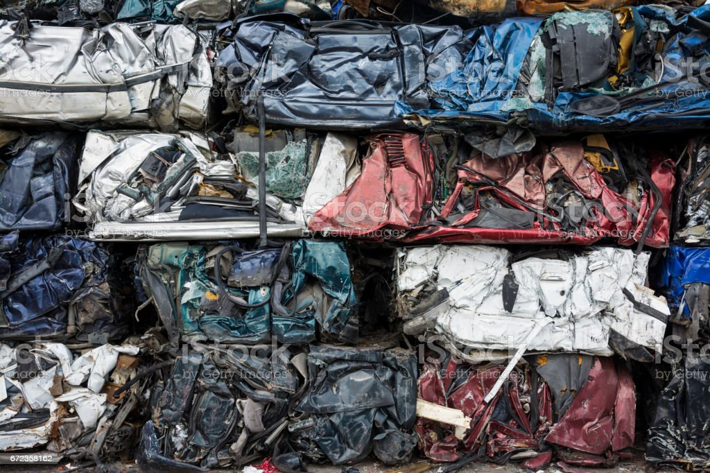 Cars in junkyard,  pressed and packed for recycling. stock photo