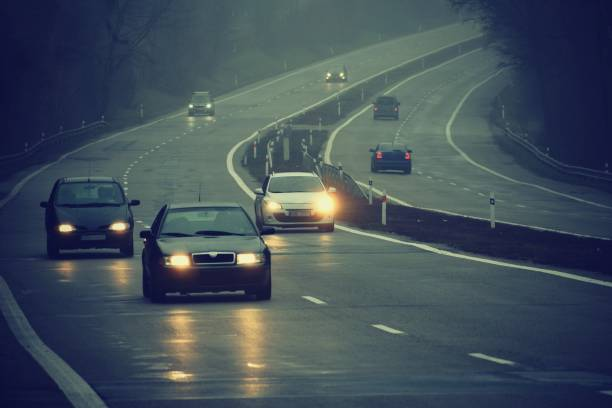 Cars in the fog. Bad winter weather and dangerous automobile traffic on the road. Light vehicles in foggy day. Cars in the fog. Bad winter weather and dangerous automobile traffic on the road. Light vehicles in foggy day. headlight stock pictures, royalty-free photos & images