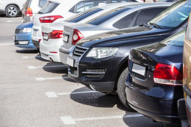 autos auf dem parkplatz - parkfläche stock-fotos und bilder