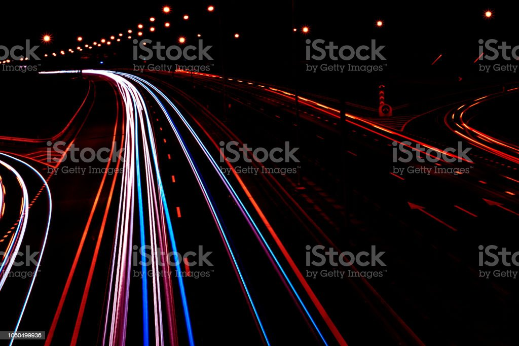 Cars light trails on a curved highway at night. Night traffic trails....