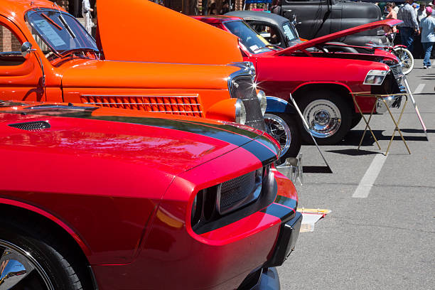 Cars lined up at a car show in Durango, Colorado Durango, Colorado, USA - June 18, 2016: Red and orange cars at a car show, lined up on the street.  The cars are muscle and vintage cars.  Some of the cars have their hoods raised.  The paint jobs on the cars are pristine, clean and shiny. car show stock pictures, royalty-free photos & images