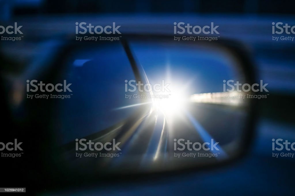 Cars long lights in rear view mirror stock photo