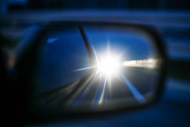 Cars long lights in rear view mirror Star reflection of cars long lights in rear view mirror at sunset. headlight stock pictures, royalty-free photos & images